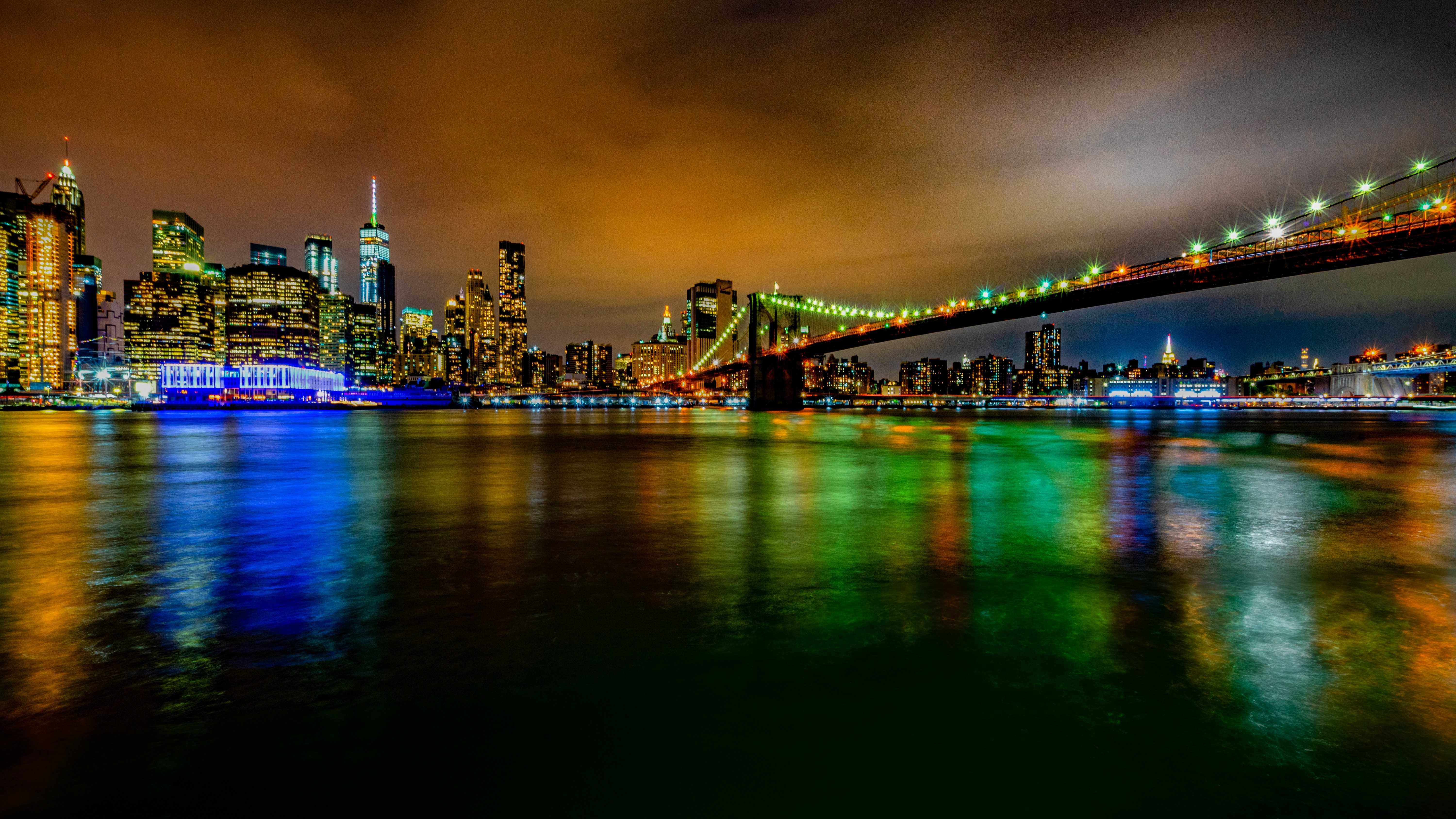 Multi-colored lights at night with buildings and a bridge