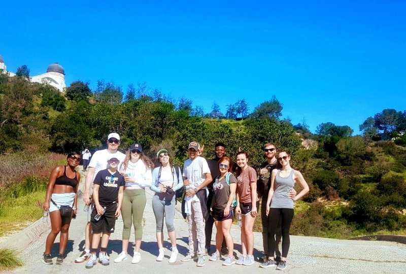 Diverse group of young people posing after a hike with Griffith Observatory in background.