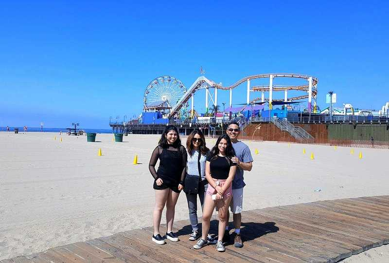 family of four standing near amusement park in los angeles beaches
