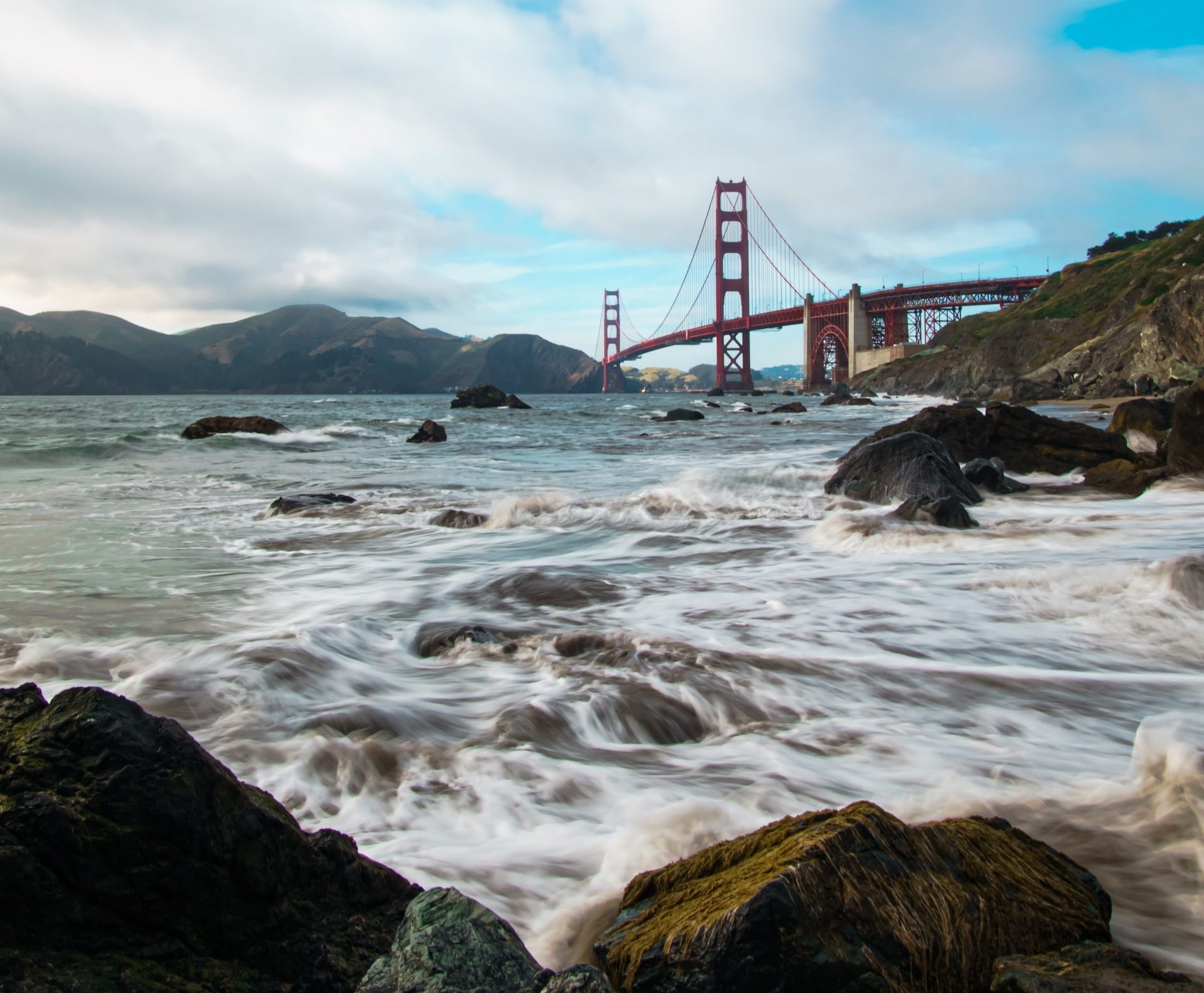 Golden Gate Bridge with a rocky beach in the foreground