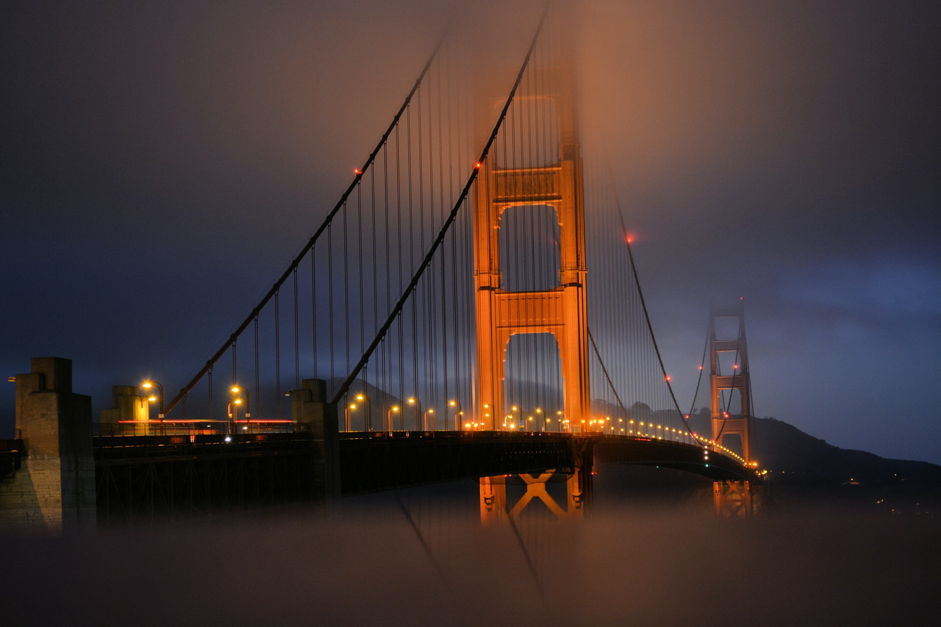 Golden Gate Bridge in the fog lit up at night