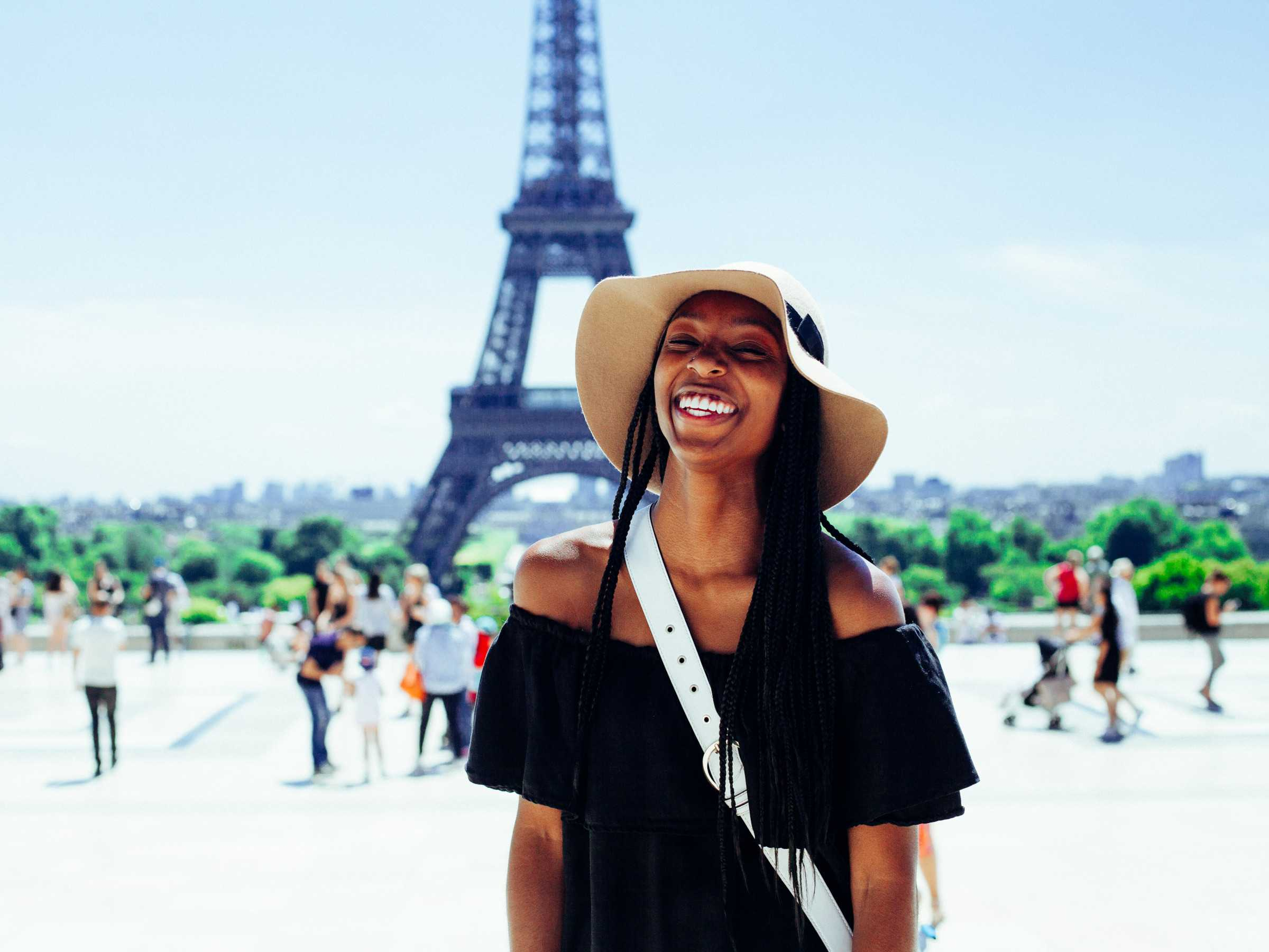 young lady wearing dark clothes and light hat smiles