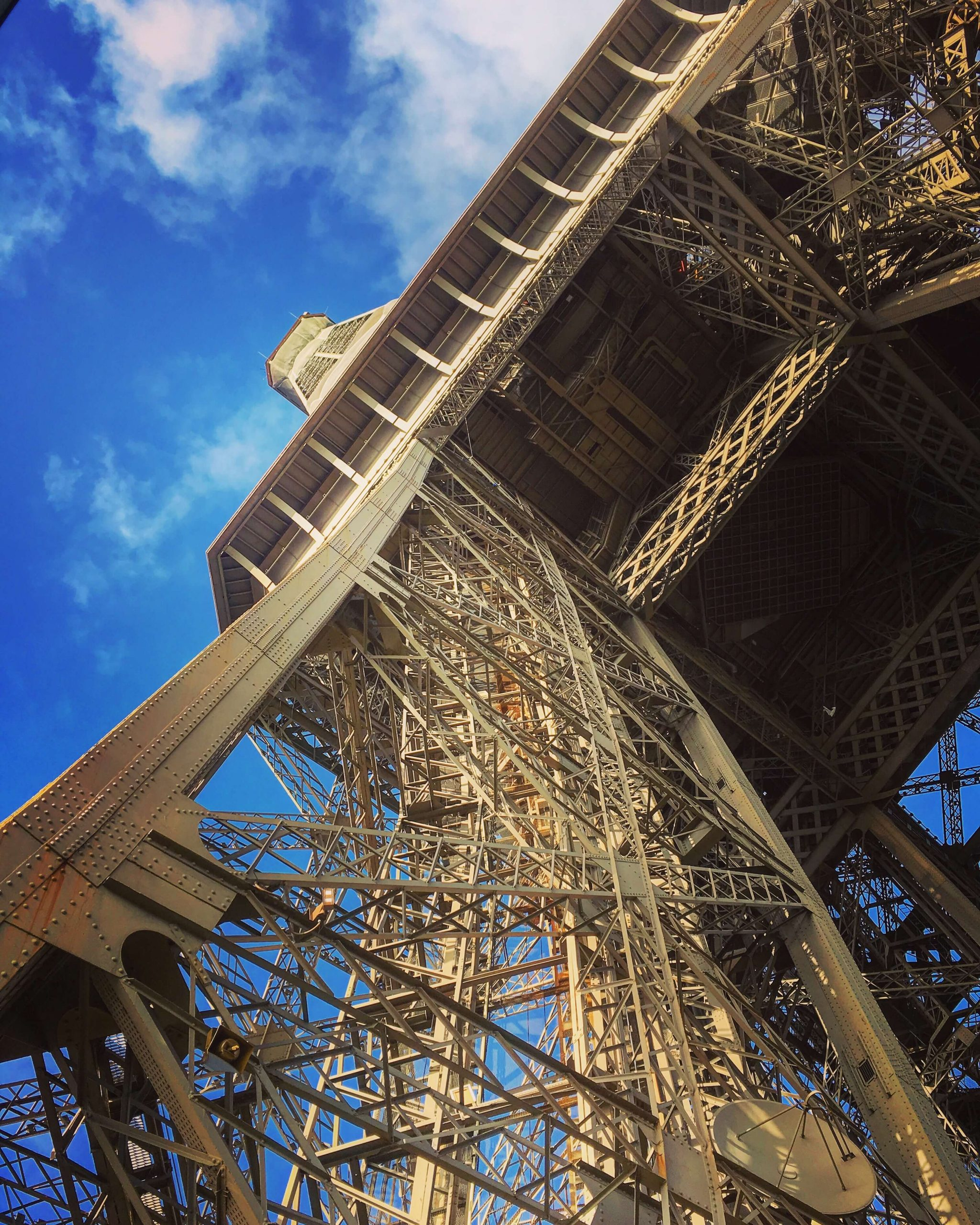 Looking up to the top of the Eiffel Tower with bright blue sky