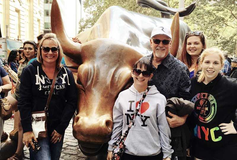 father mother and three daughters stand near the charging bull statue in the Financial District