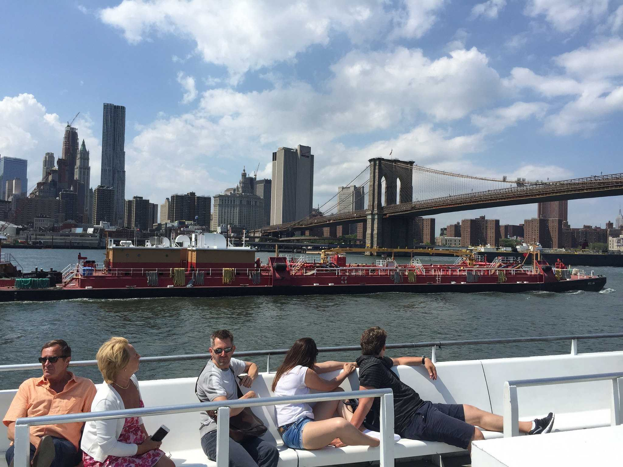 People riding on a boat past the brooklyn bridge