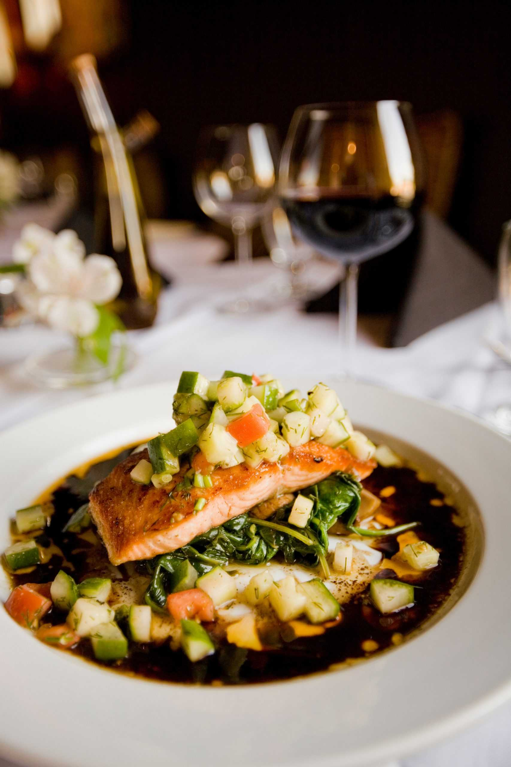 Salmon and vegetables on a plate and glass of red wine