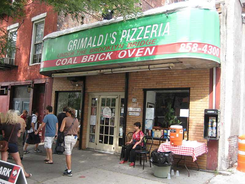 Pizza Restaurant with people walking by it