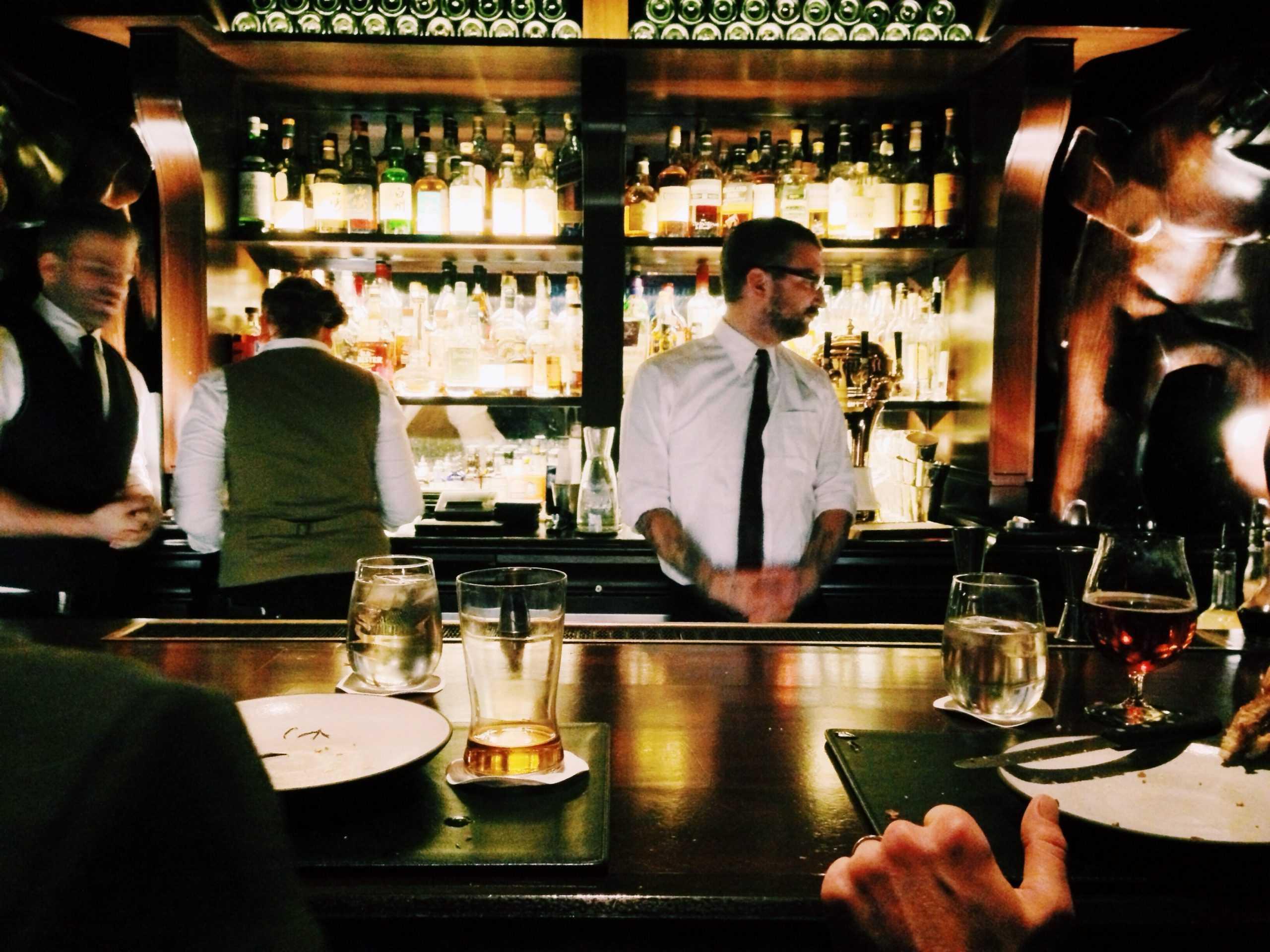 Bartender standing next to bar