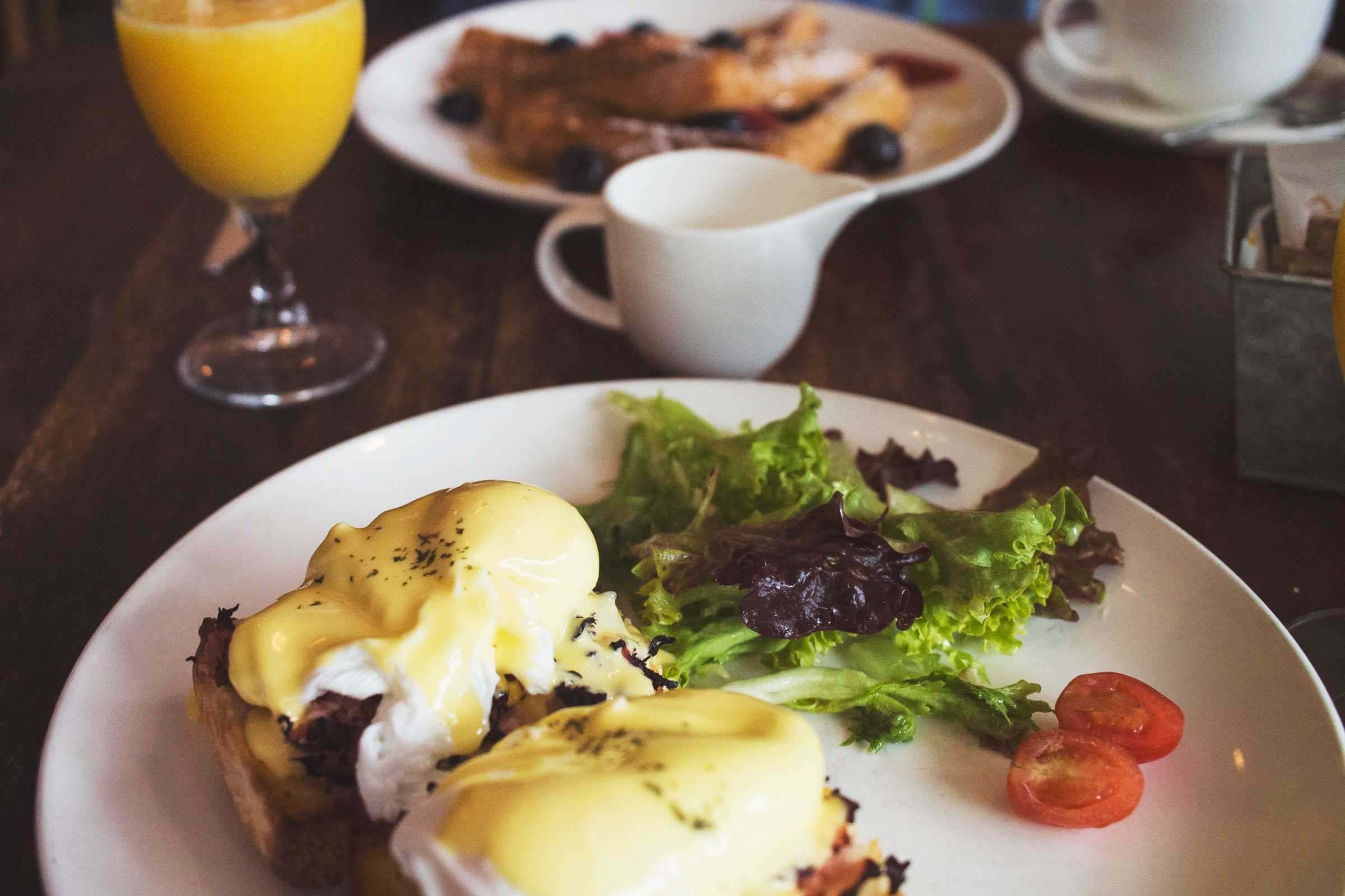 Plate of eggs benedict and side salad with glass of orange juice