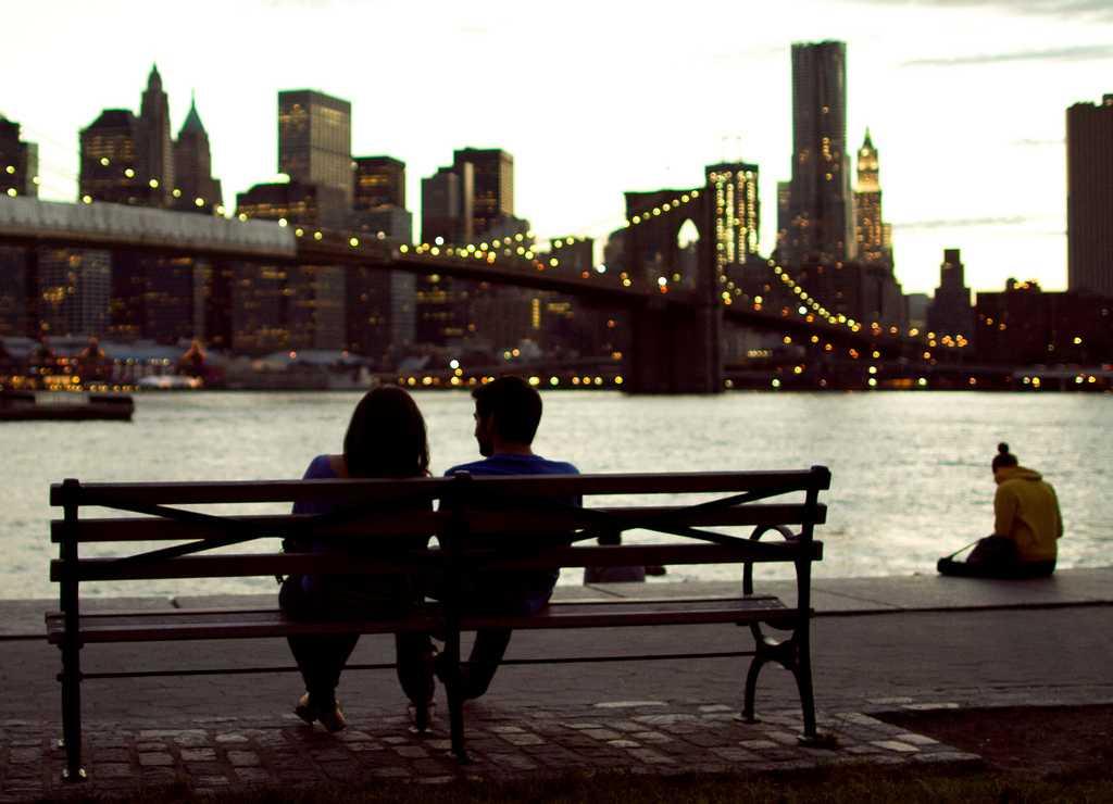 couple sitting on bench overlooking NYC