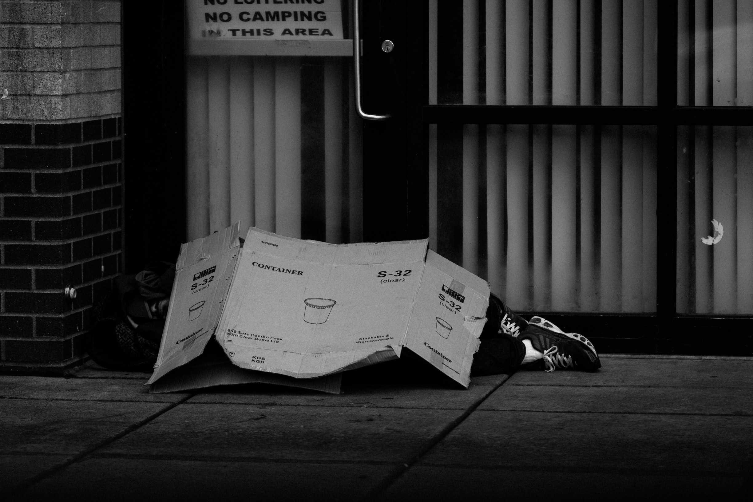 man sleeping under cardboard