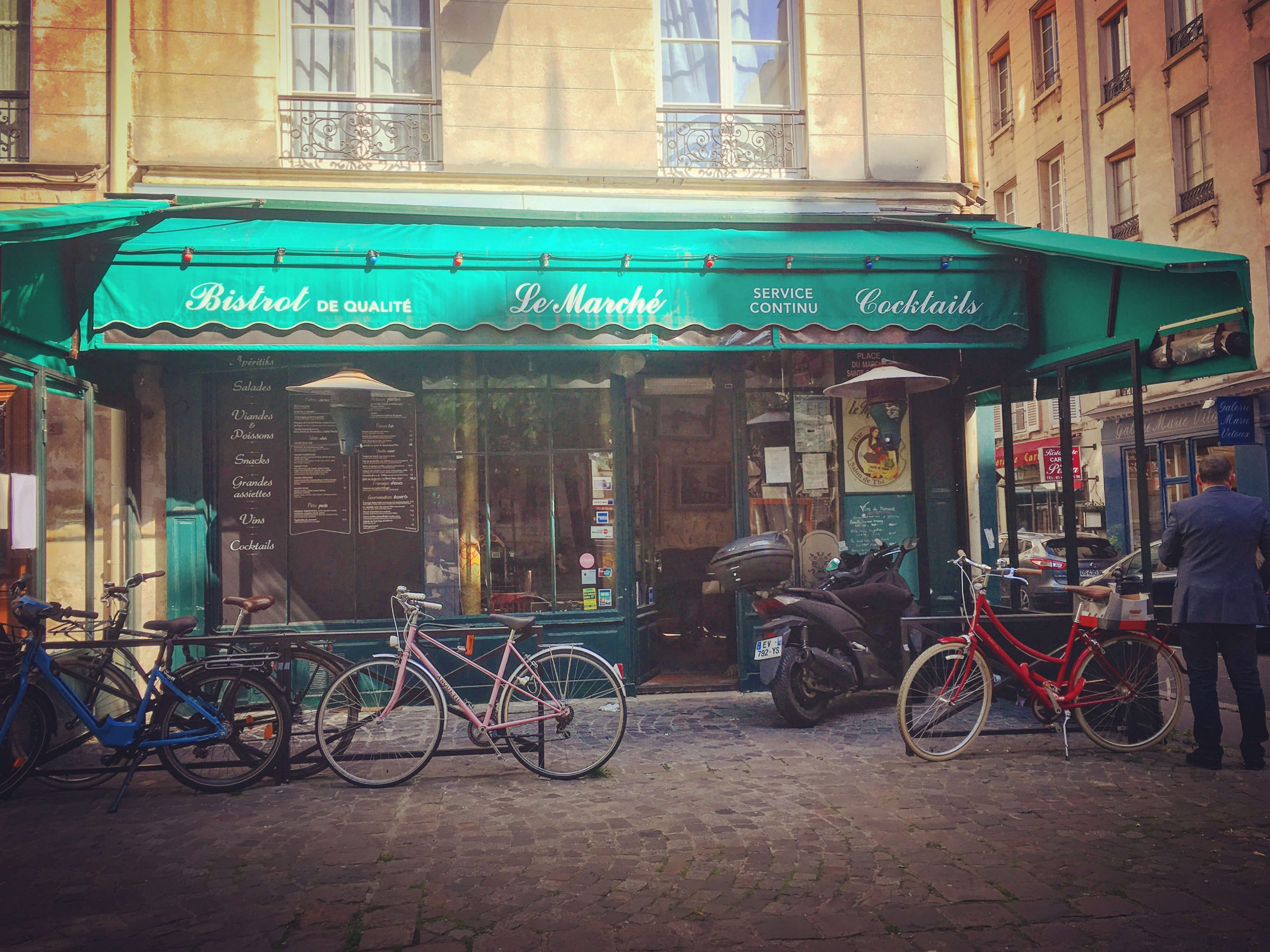 Green awning for bistro Le Marche with bicycles parked outside