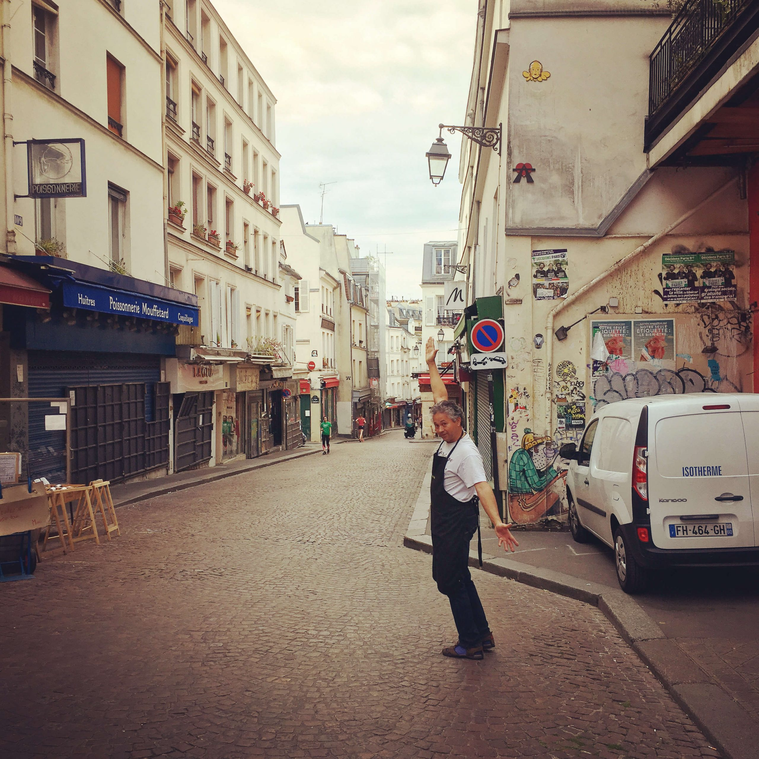 Smiling man with arms in the air on rue Mouffetard in Paris