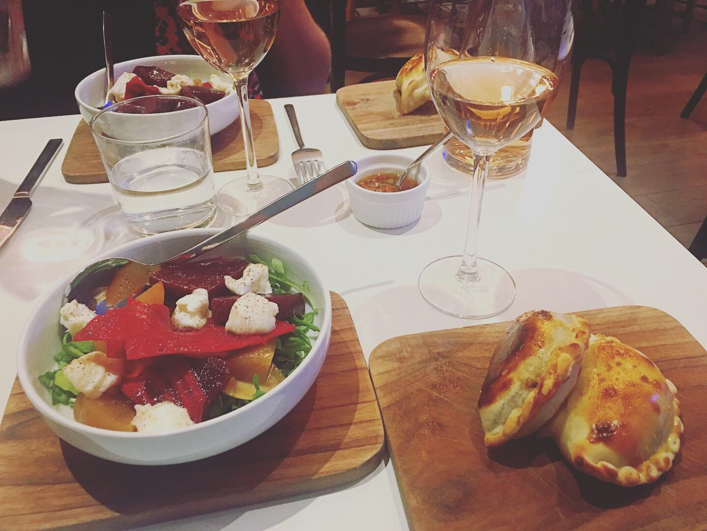 Empanadas, a small salad and wine set at the table