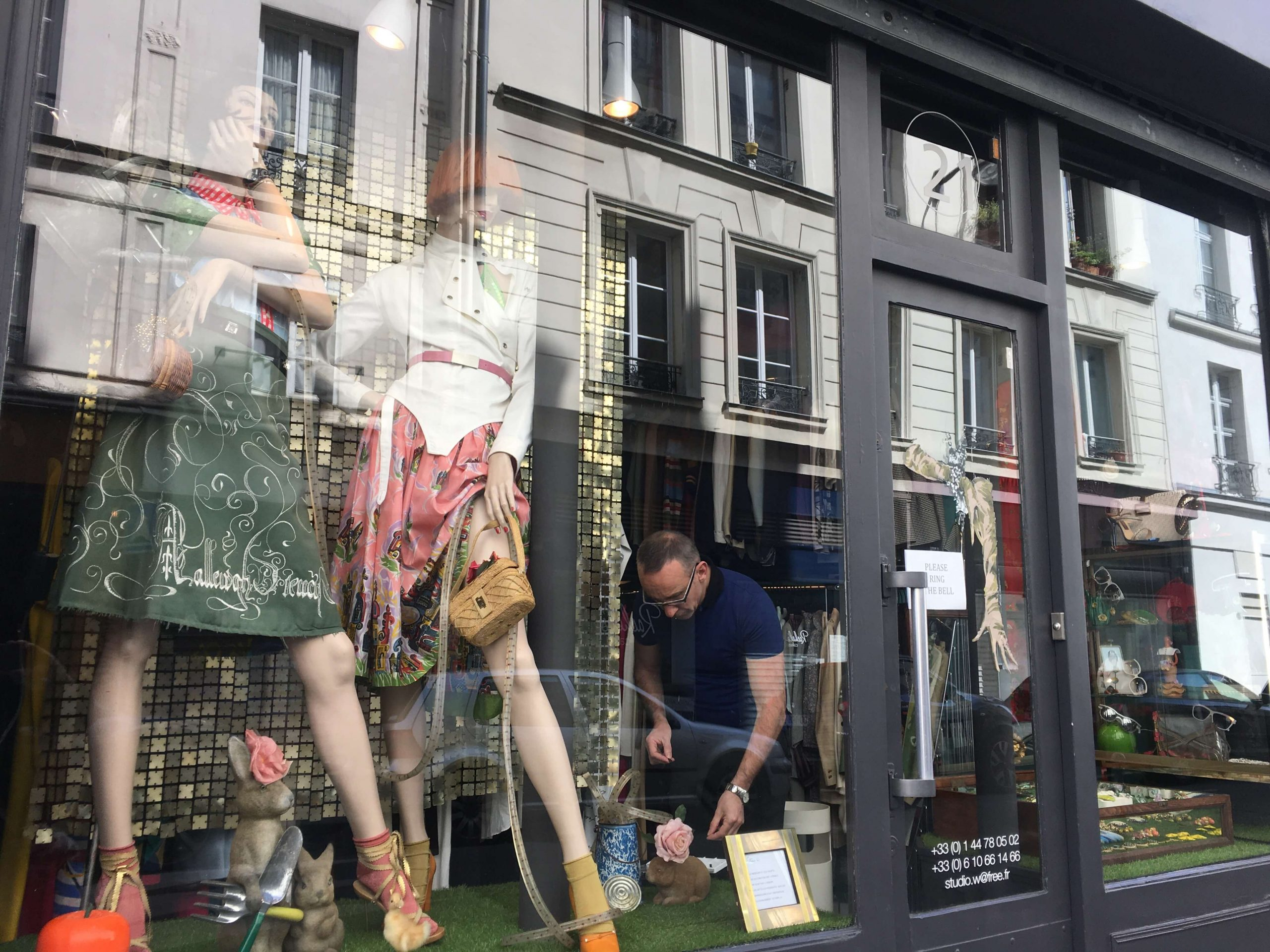 Man fixng a display with two mannequins dressed in vintage dresses in a shop window