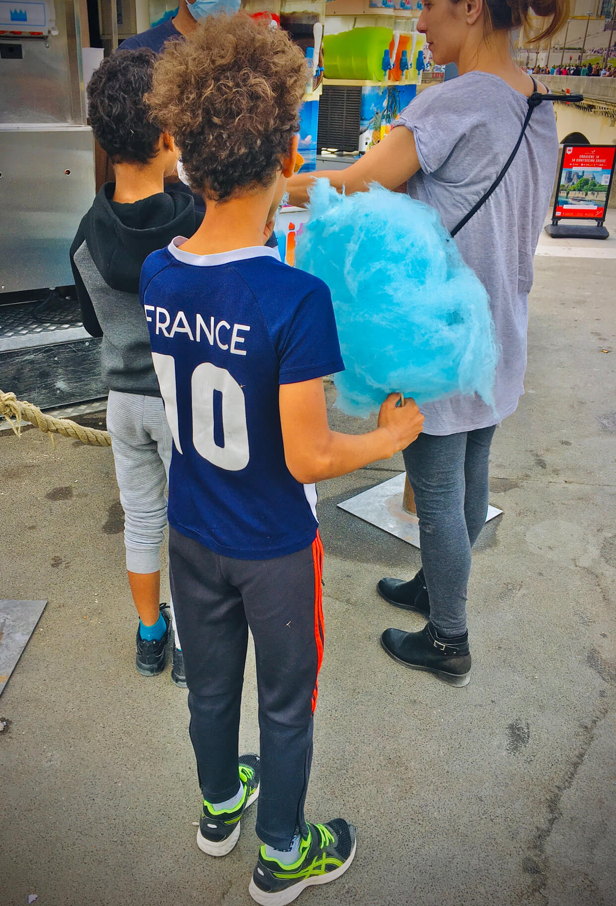 A boy with a jersey that says France 10 eats a big, blue puff of cotton candy