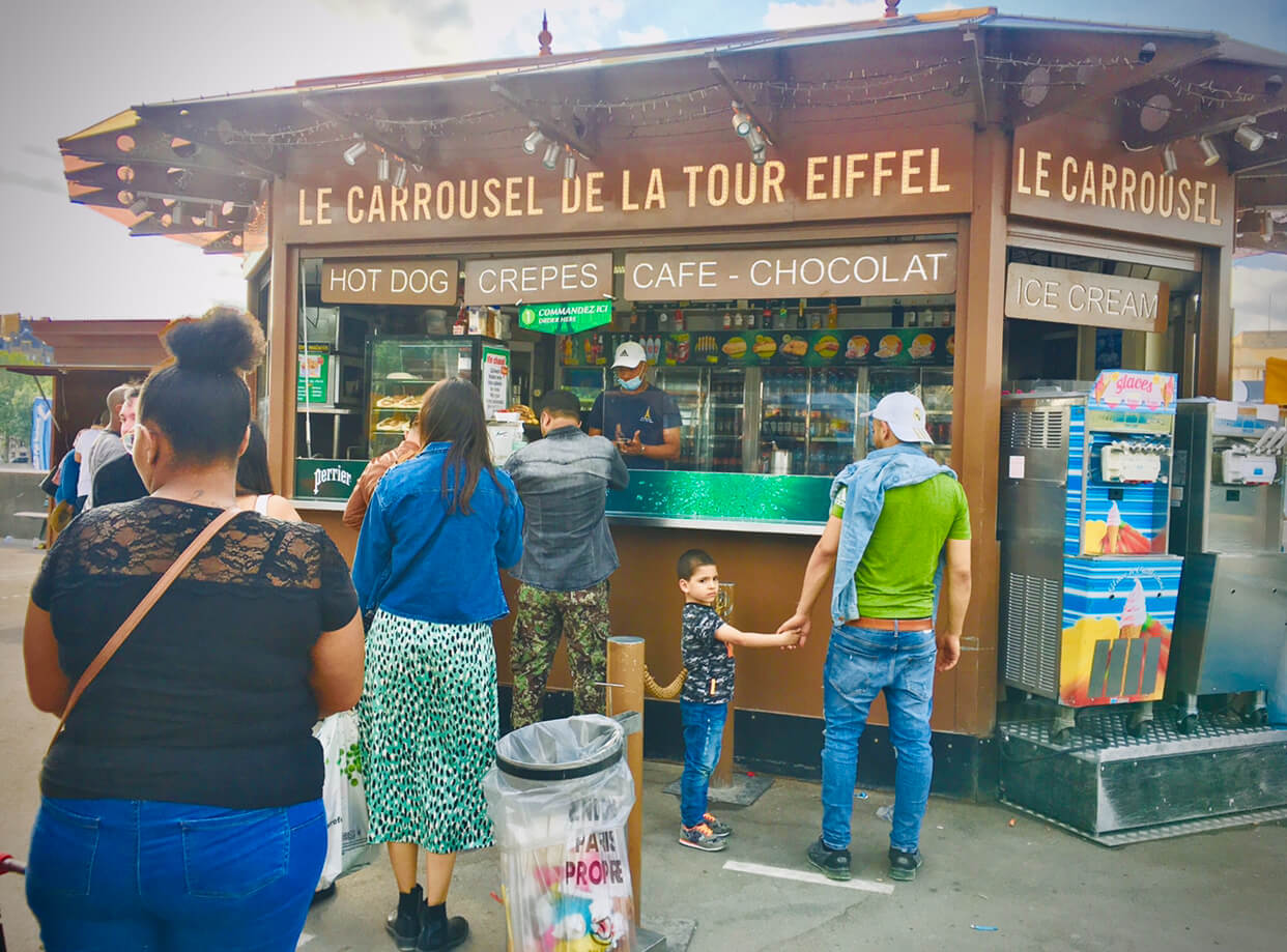 People stand in line at a kiosk to order hot dogs, crepes, coffee, chocolate