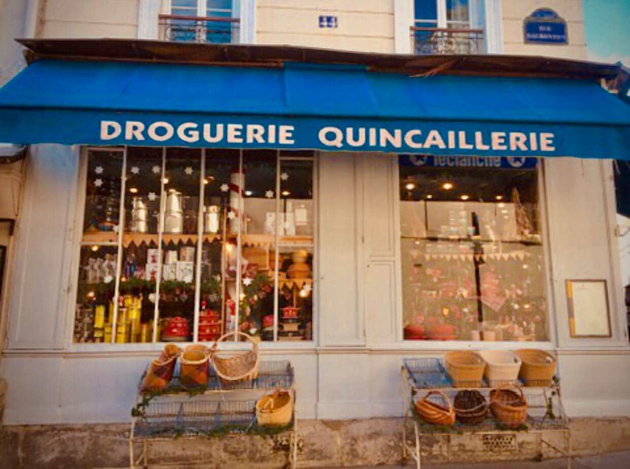 Blue awning over two windows says Droguerie Quincaillerie. Baskets sit on shelves on the sidewalk