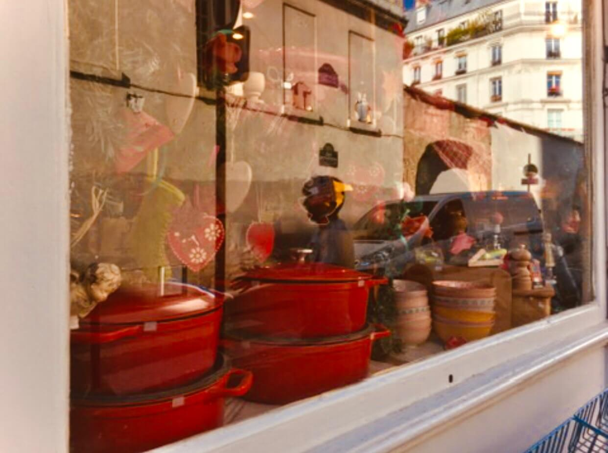 Red dutch oven cookware and bowls and ornaments on display in a window