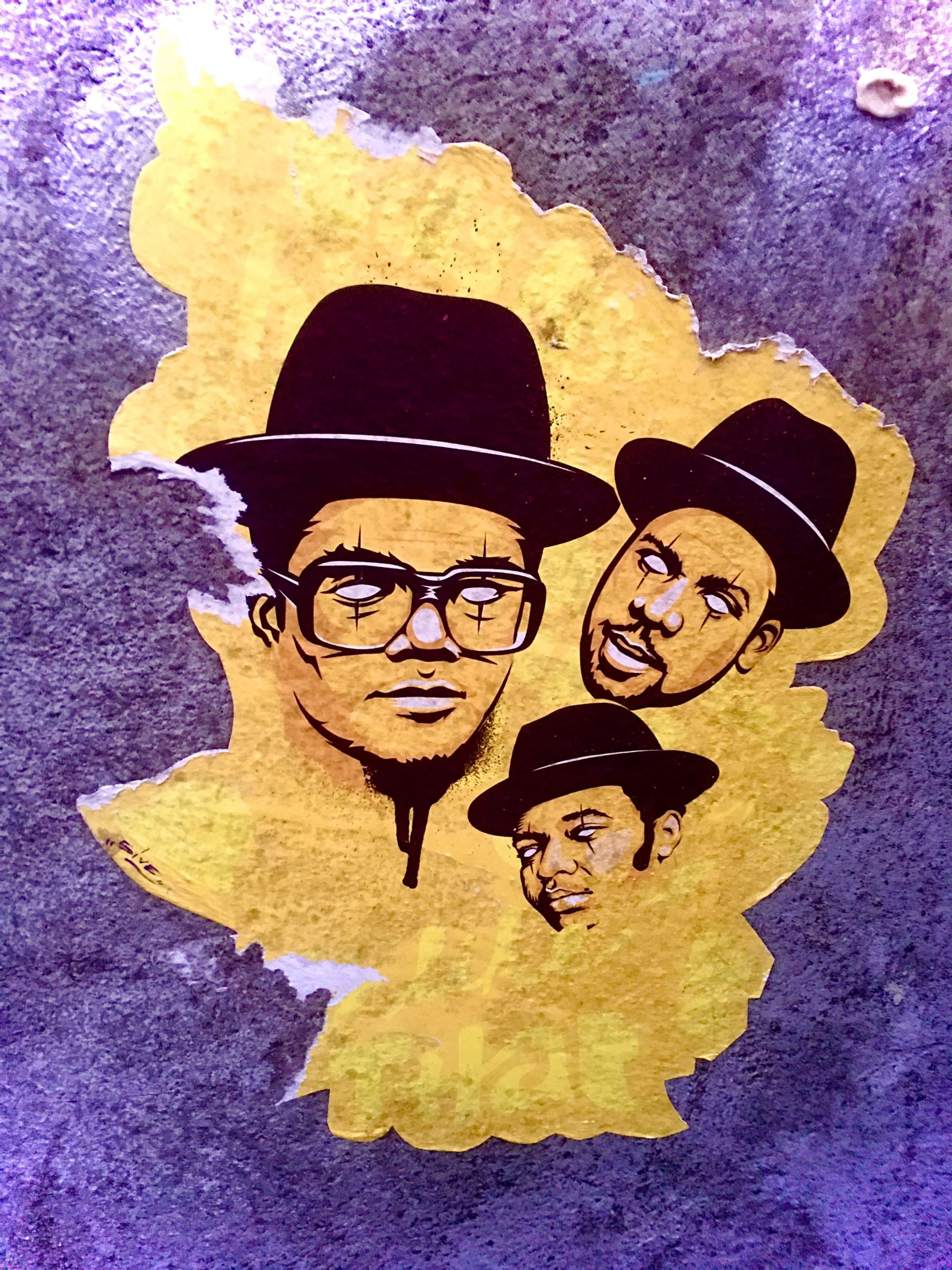 Run DMC wearing black fedoras in a street art piece
