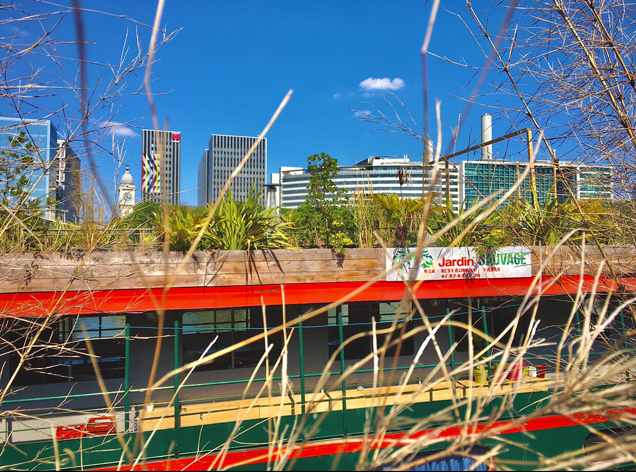 A boat named Jardin Sauvage with many green plants and the city skyline behind it with a bright blue sky