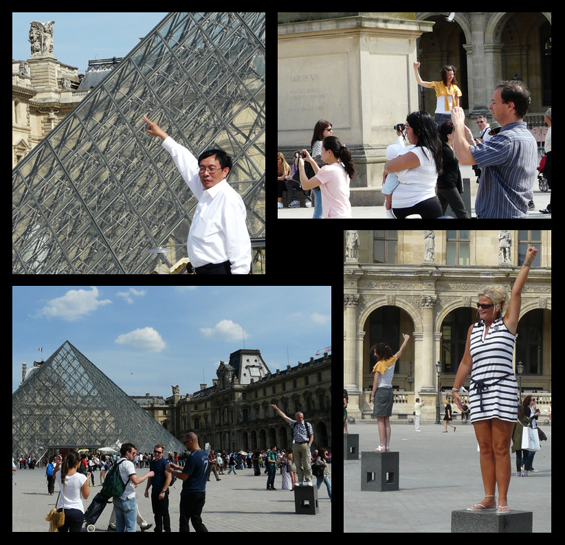 Lots of tourists posing in front of the Louvre pyramids.