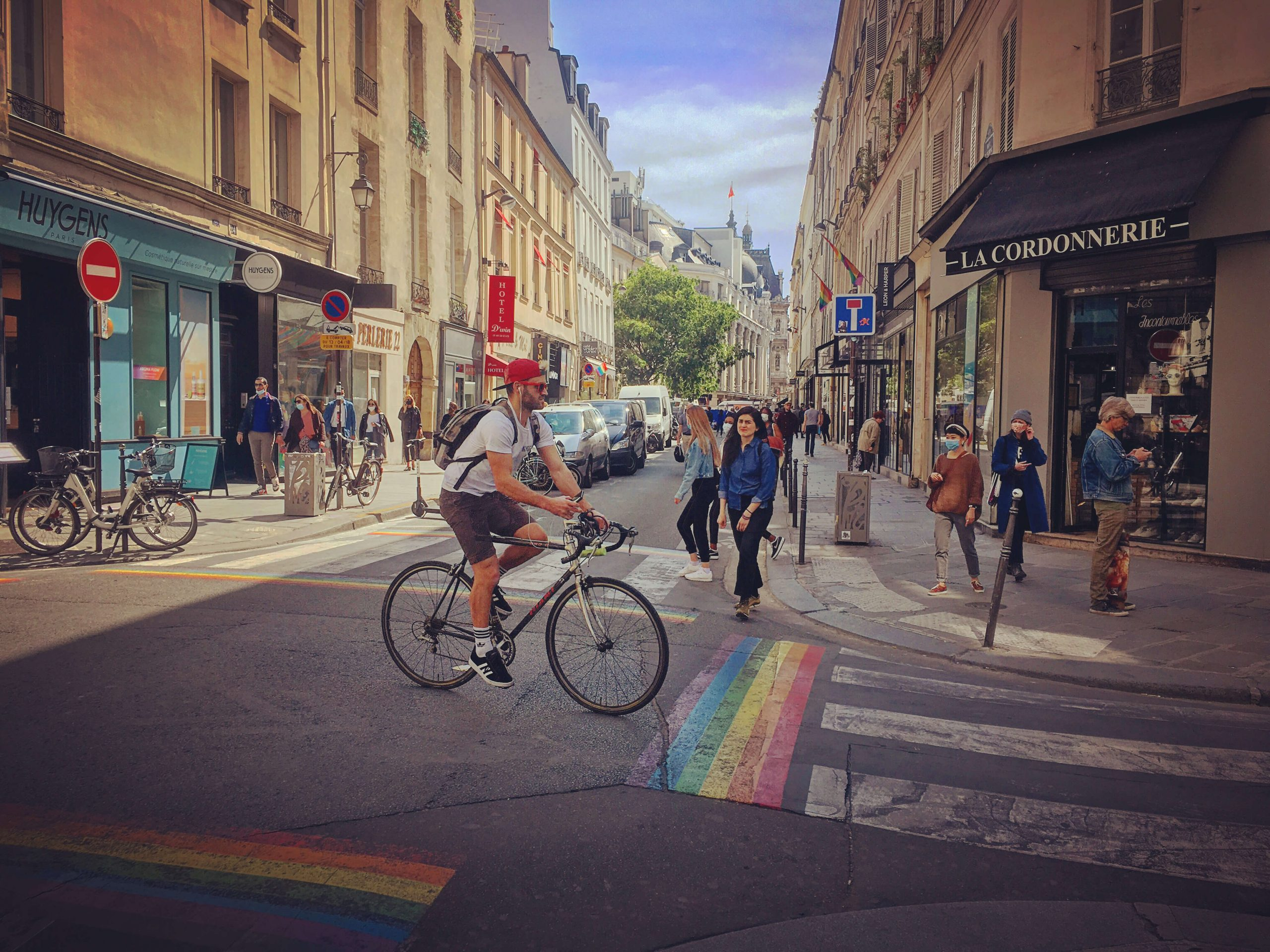 Man riding a bicycle through intersection with rainbow crosswalks
