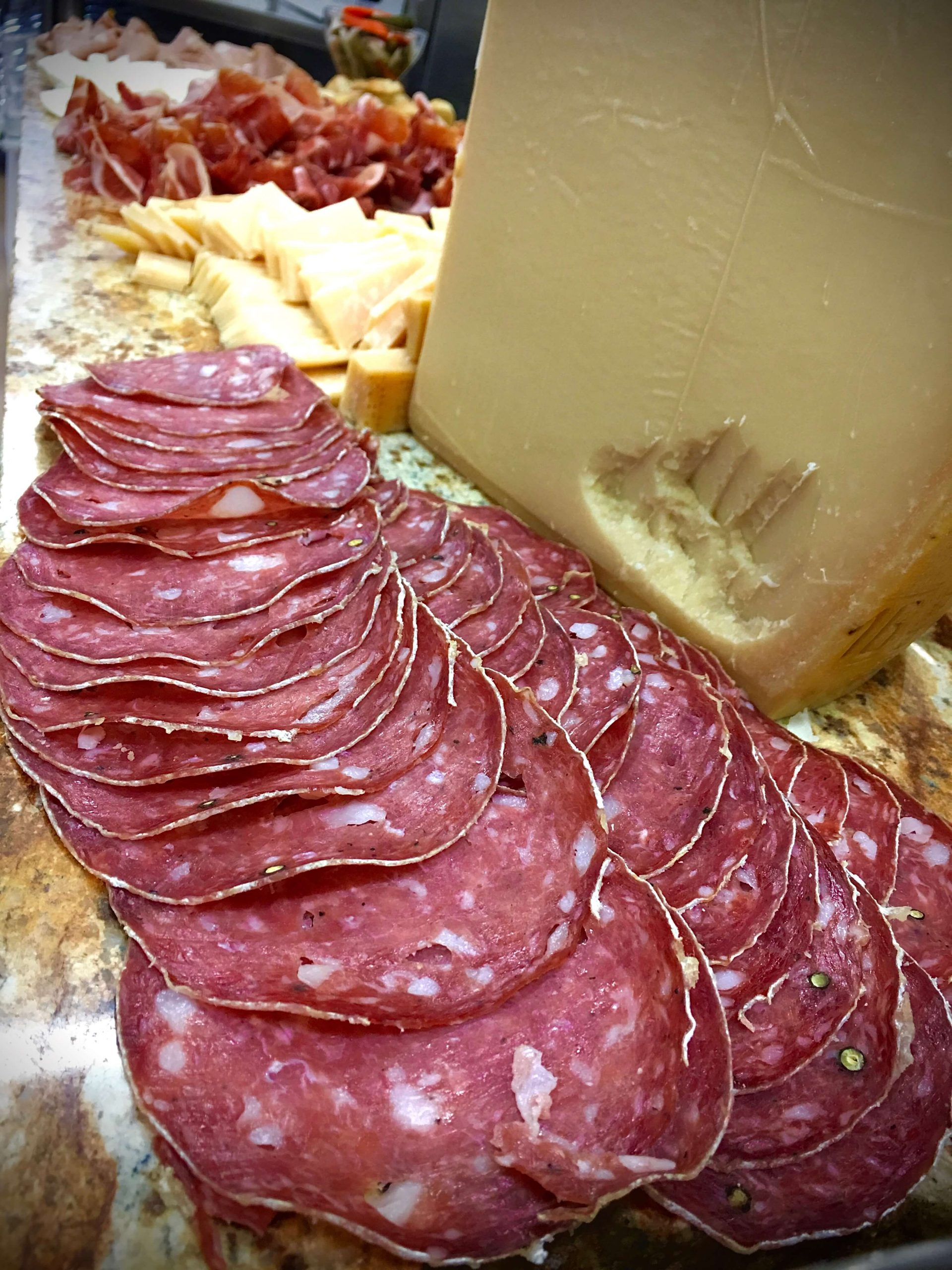 Sliced salami and a hunk of pareggiano reggiano cheese