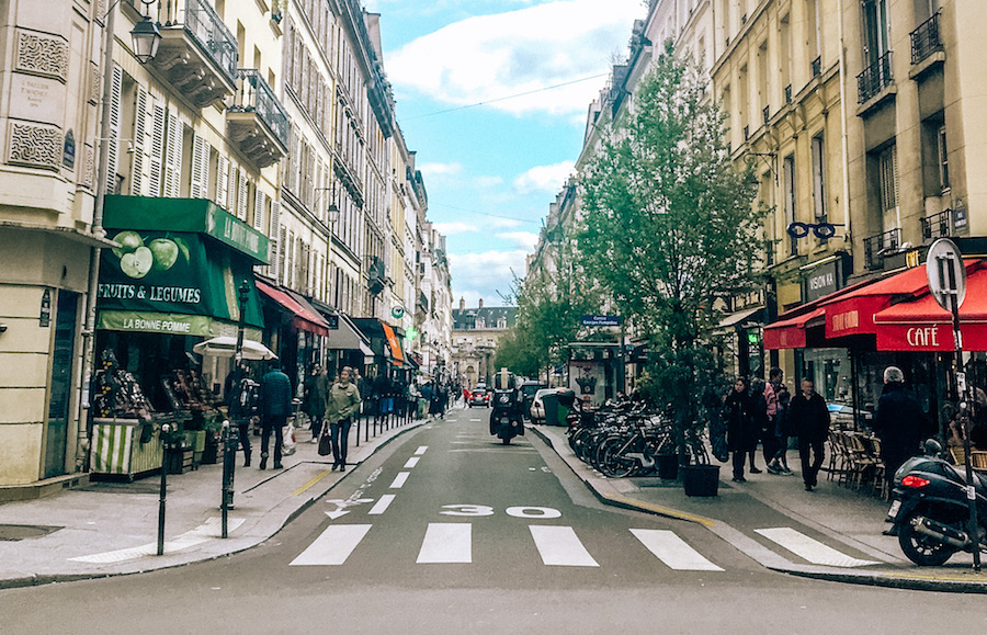 A scene from the streets of Paris with pedestrians, scooters, and shops