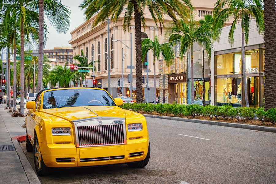 A yellow colored Rolls-Royce Phantom convertible parked on Rodeo Drive with luxury stores in the background in Beverly Hills, Los Angeles, California