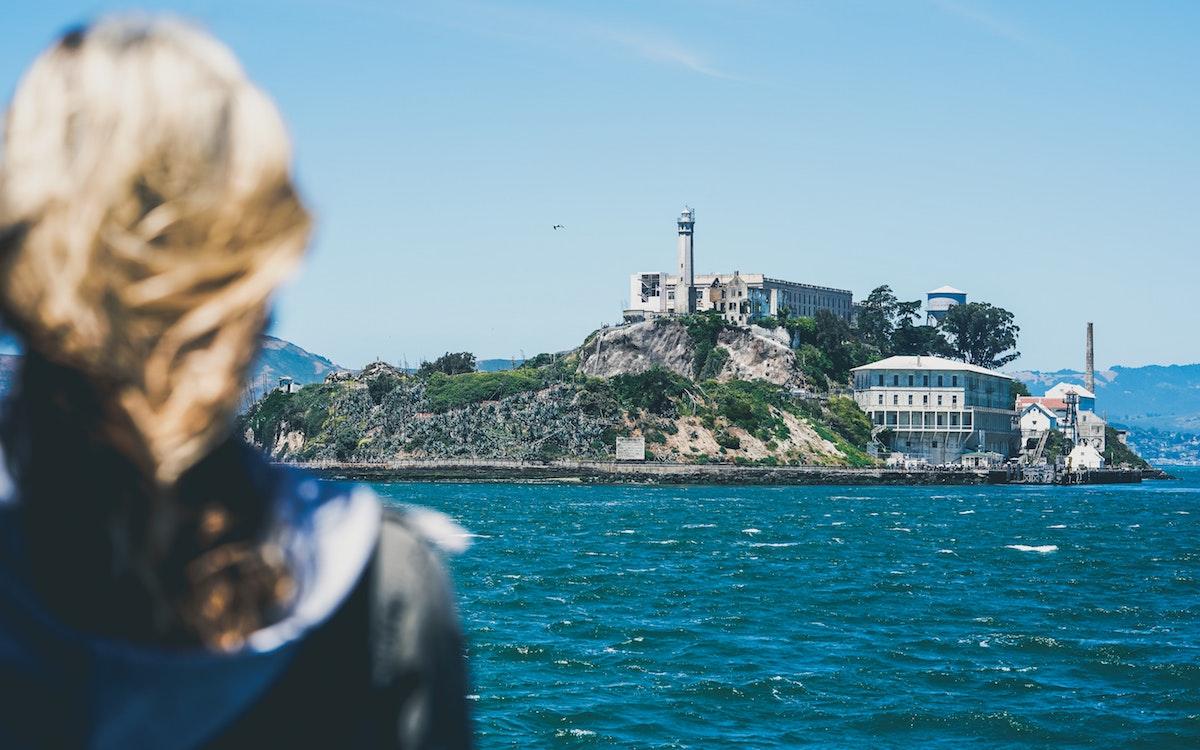 Woman looking at alcatraz island from on board the alcatraz cruise