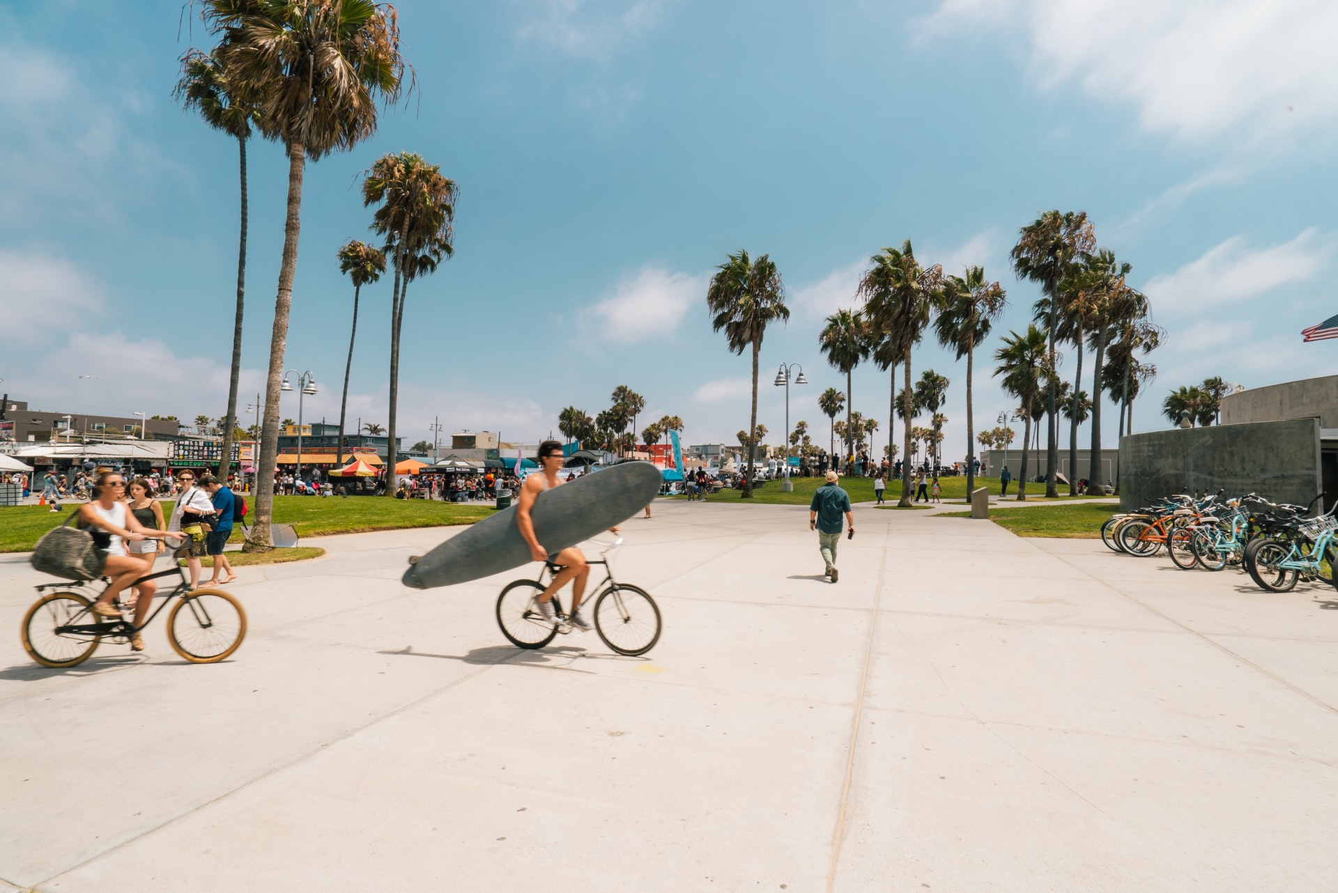 surfer and bicyclists at venice beach, california