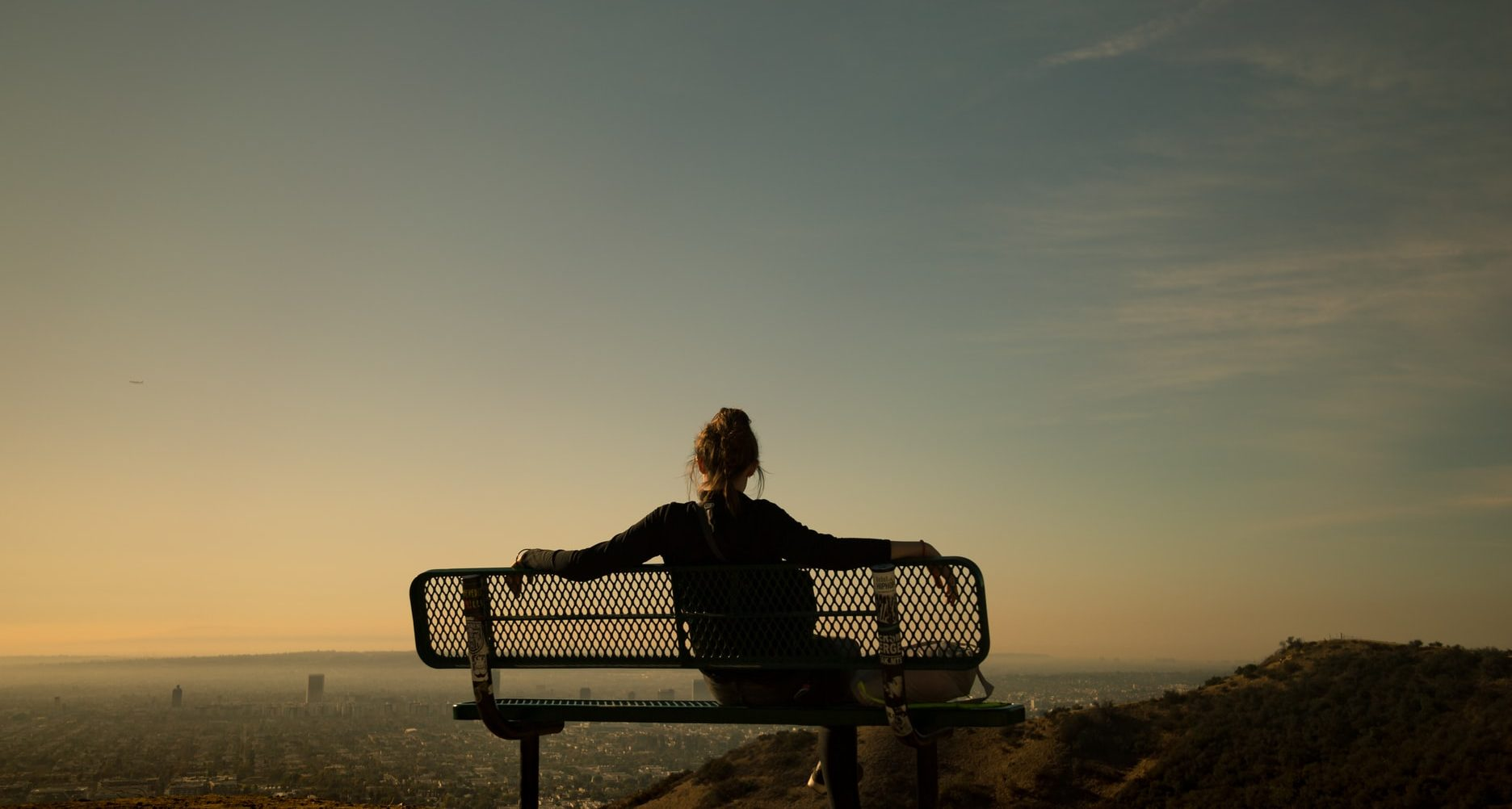 woman sitting on a bench at Runyon Canyon Park at sunset