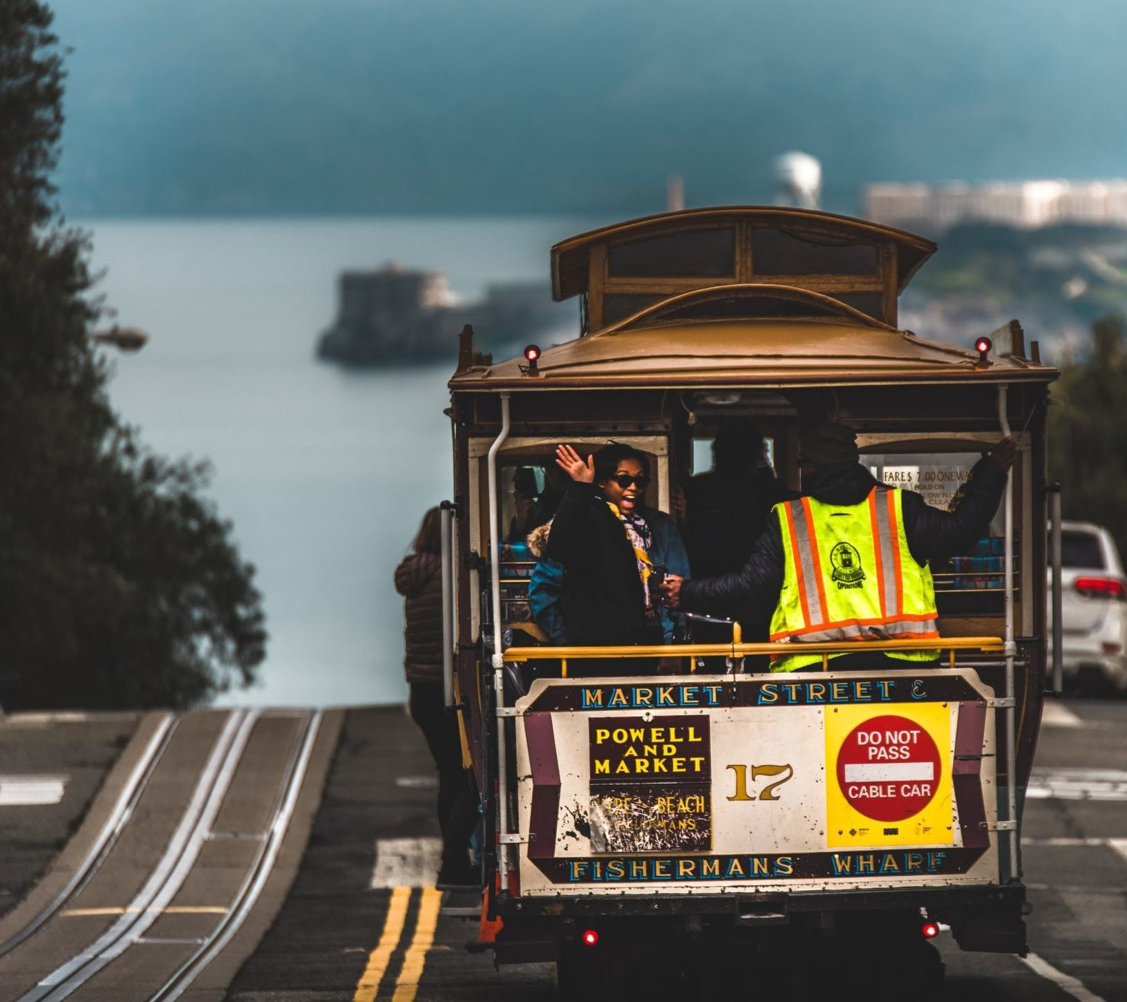Woman waving out of the back of a San Francisco cable car
