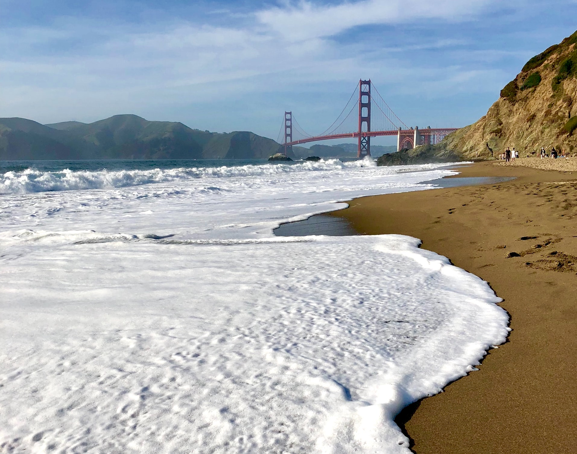 Baker Beach with waves in the foreground and Golden Gate Bridge in the distance as photographed from the Presidio of SF