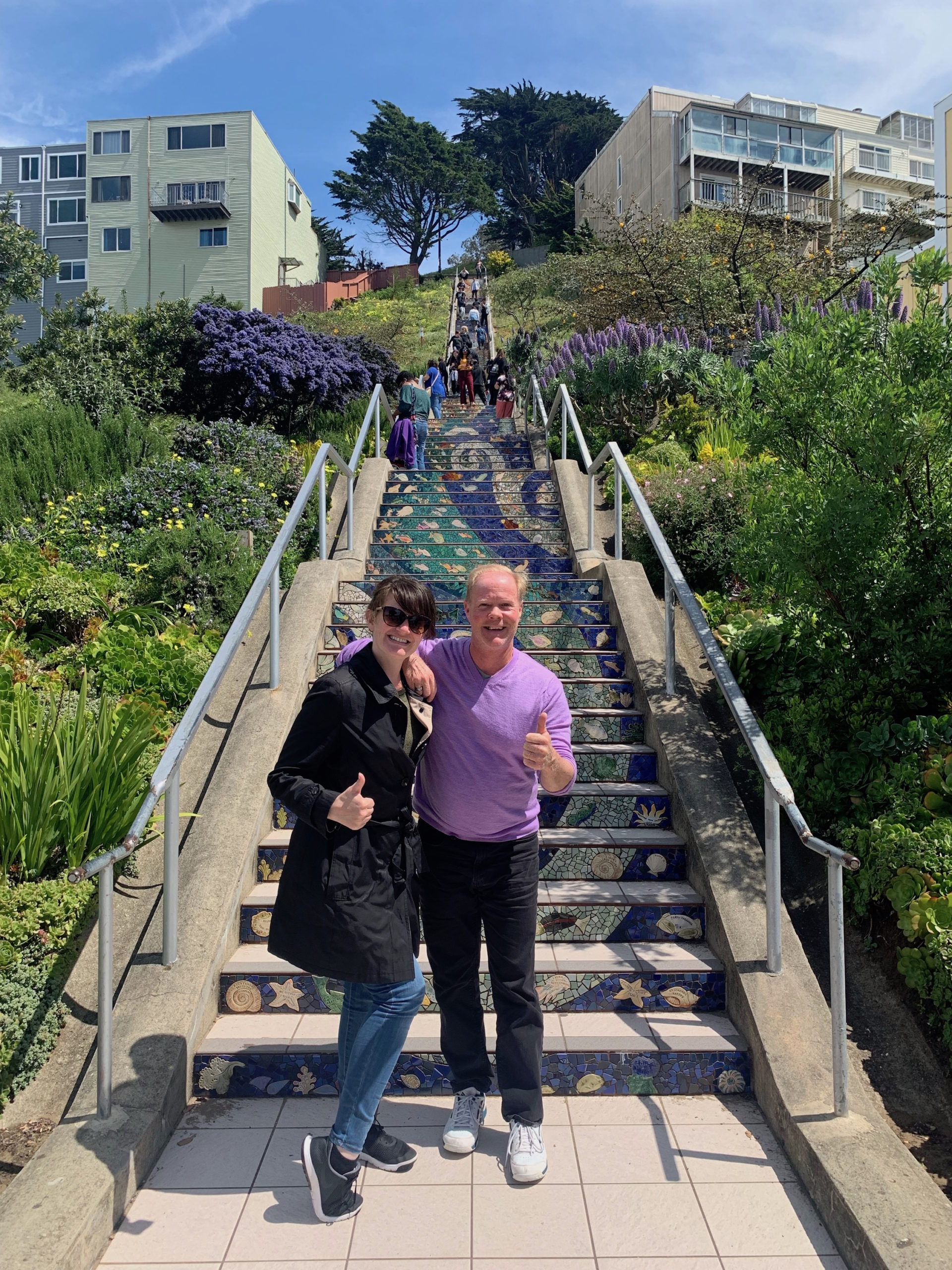 Two people posing for a photo in front of the 16th Avenue Tiled Steps