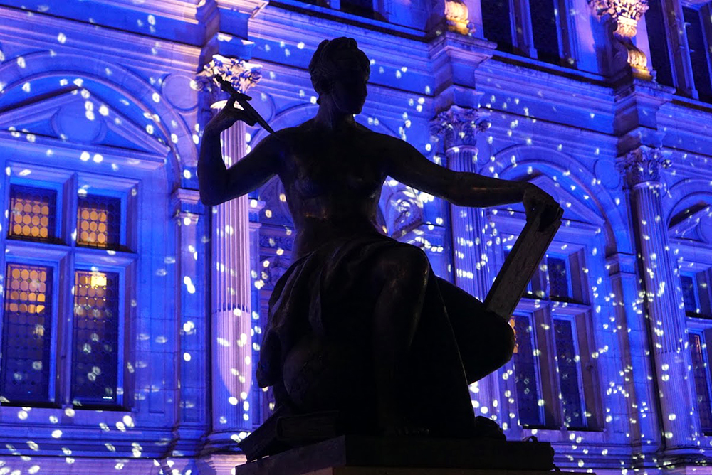 Statue in front the Hôtel de Ville in Paris lit with holiday lights