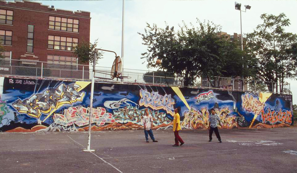 boys playing basketball by a graffiti-covered wall in the bronx