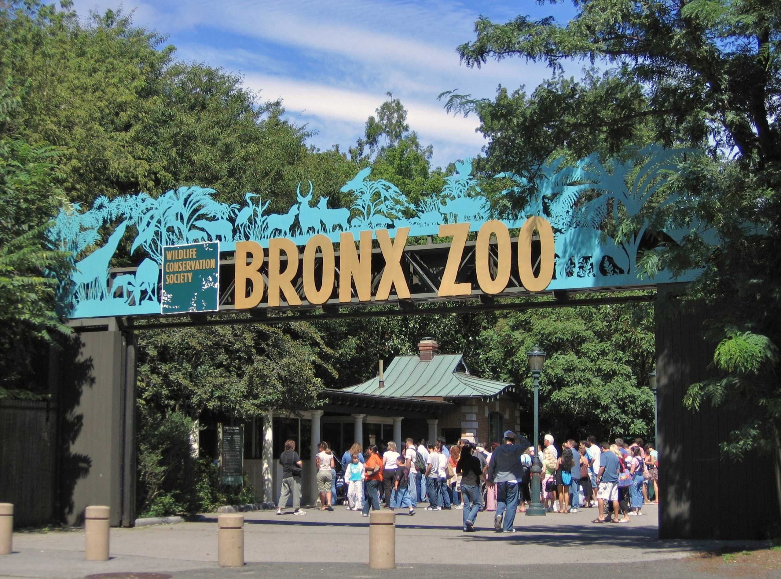Bronx Zoo Sign, people standing underneath it