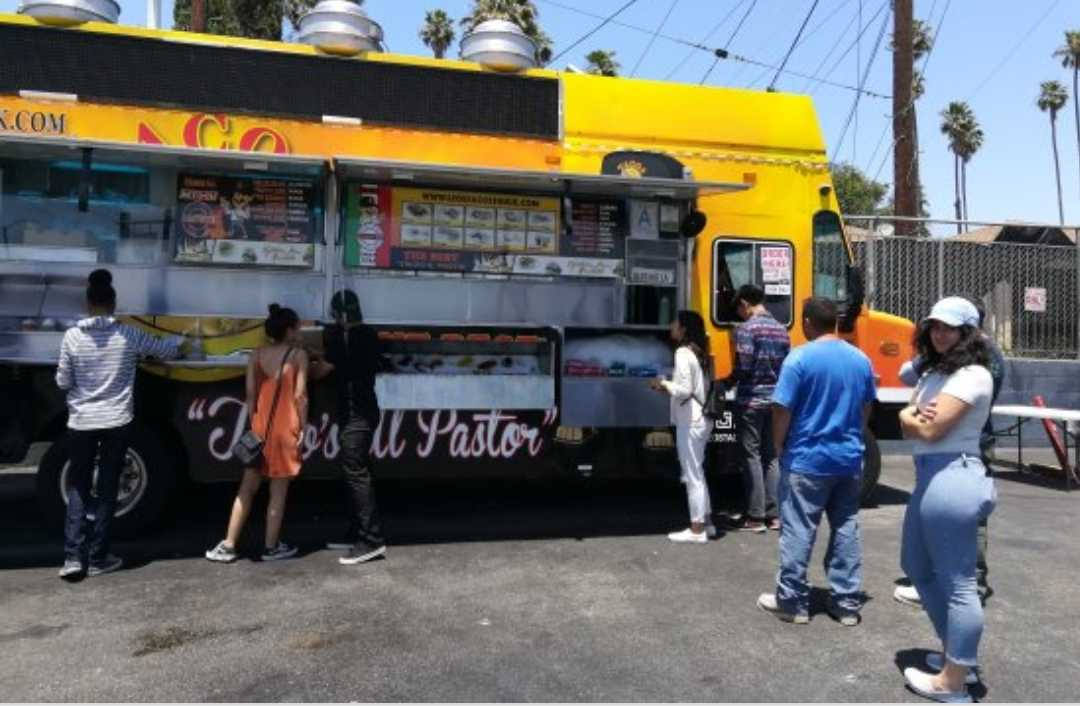 People standing in front of a food truck