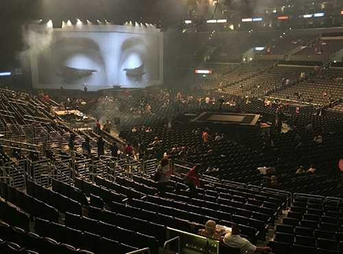 Concert seats, stage, big screen with woman's eyes