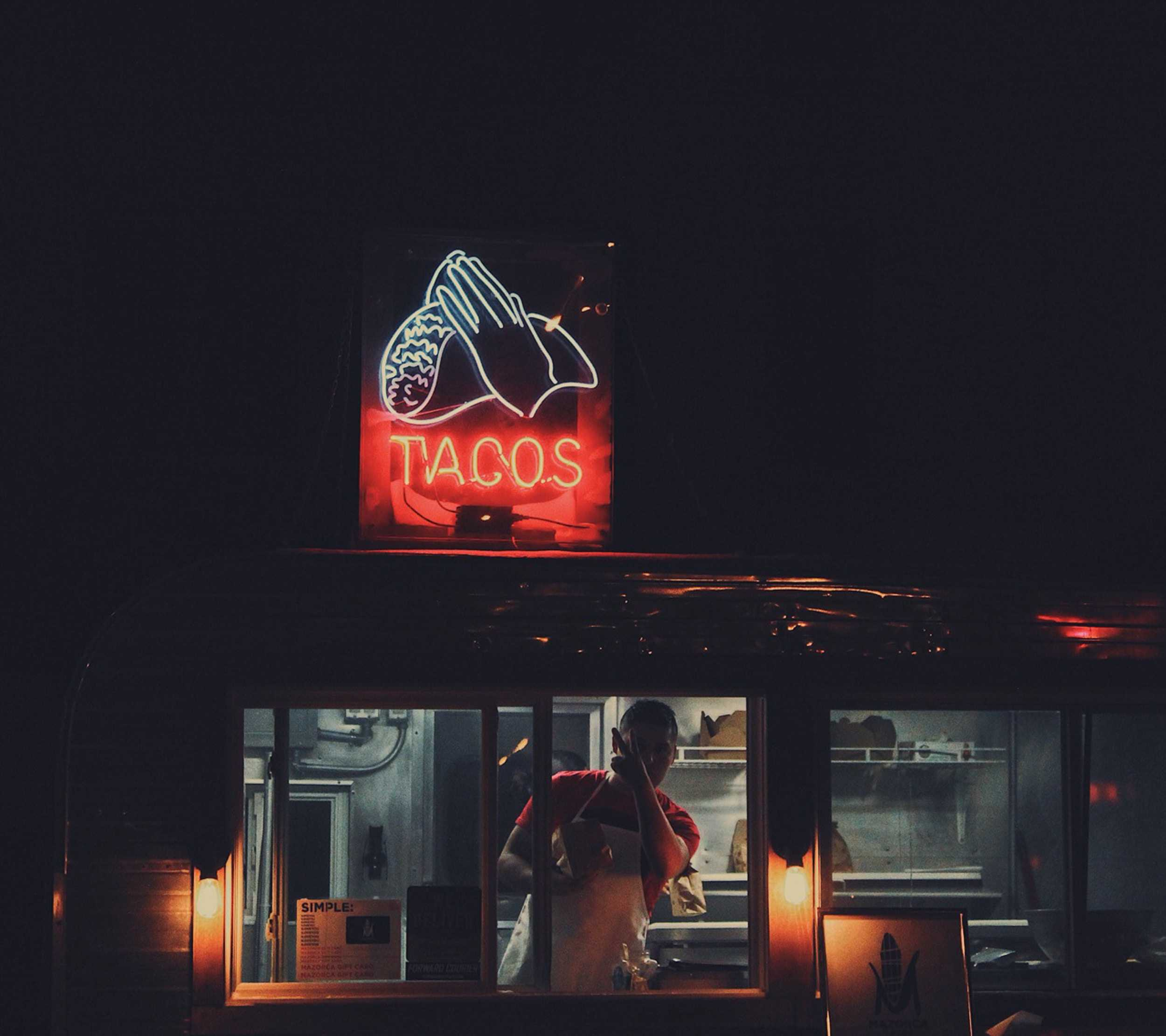 Lights that say taco and a man behind a window