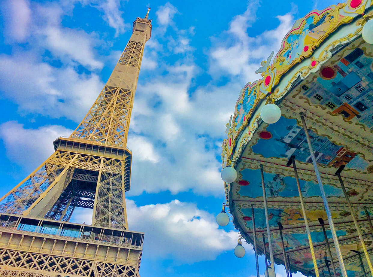 The Eiffel Tower and a portion of a carousel with a vibrant blue sky with fluffly white clouds