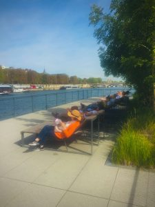relaxing in chaise lounges next to the Seine in Paris